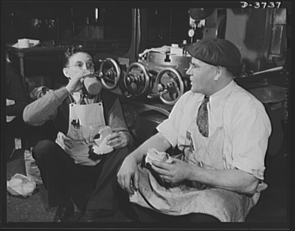 """A meal on the march. Machine hands in the tool and die room of a converted automobile plant take lunch periods right on the job. The slotting machine behind them perforates metal shapes used in the production of army """"jeeps"""" and tanks. Ford Lincoln plant, Michigan"""