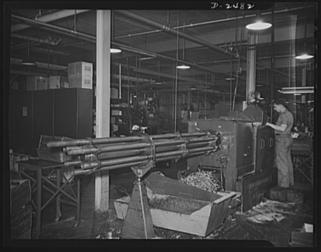 A New Britain-Gridley lathe is worked by an experienced operator at a Midwestern company. The machine which formerly made spur gears, worm wheels and commentator rings has been converted to war use by being tooled with an eccentric spindle and thread rolling attachment for the production of twenty-millimeter shell boosters