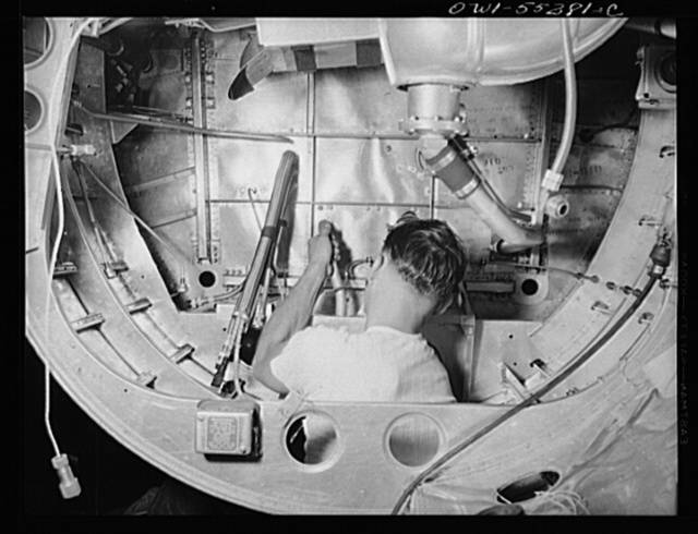 A North American employee assembles the landing gear mechanism inside the nacells of a B-25 bomber