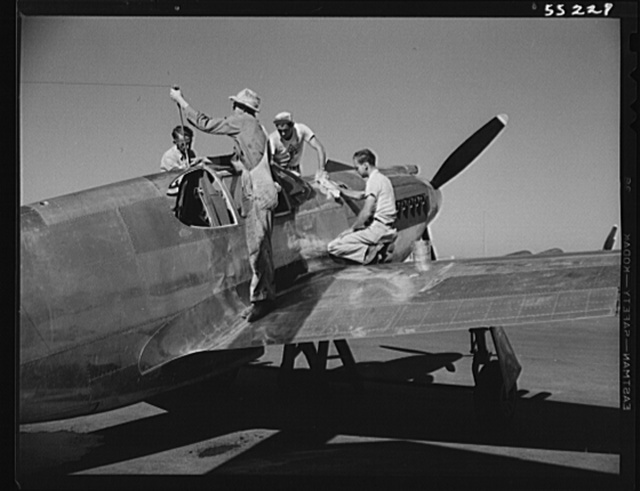 A North American P-51 fighter is cleaned by painters before receiving the olive drab paint of the United States Army Air Forces