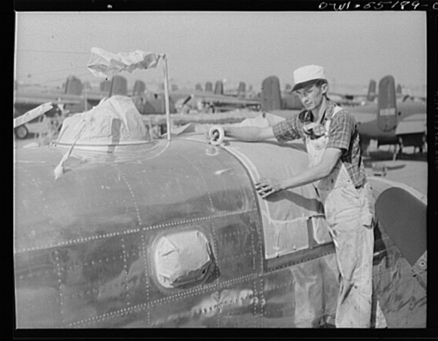 A painter on the flight ramp marks off the transparent enclosure on a North American B-25 bomber before adding the camouflage paint of the United States Army Air Force. Windows covered with brown paper