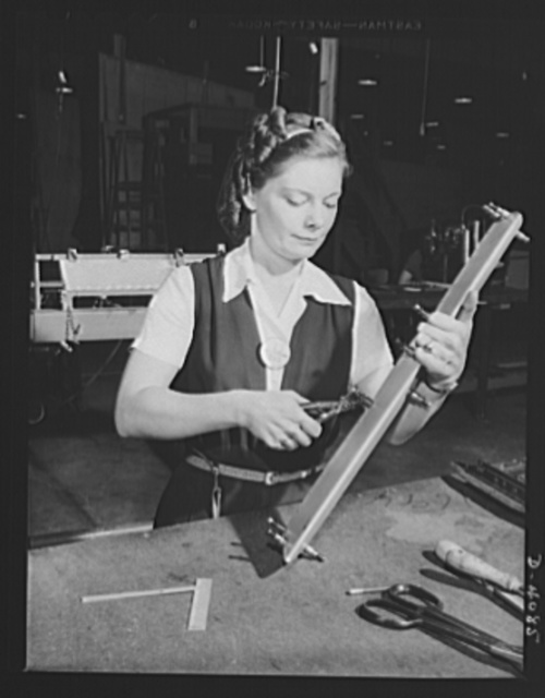 A Pearl Harbor widow gives her complete effort toward defeating the murderers of her husband. Mrs. C. Margaret Bailey starts the assembly of a bomber tail surface trimming tab in a West Coast airplane factory. She has been working here since the first of the year and is glad that this vital work supports her son and daugher -- aged seven and five -- so that she will not be obliged to accept relief from the Navy