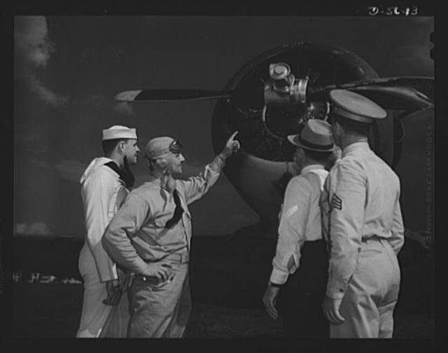 """A poster comes to life. A couple of groundhogs get a liberal education from a Navy pilot as Aviation-radio Chief John Marshall Evans (left) escorts welder George Woolslayer and Sergeant French L. Vineyard (right) through his navy post. The three colleagues of the """"Men Working Together"""" poster learned how the war can be won only by the united efforts of soldier, sailor and worker, during their introductions to one another's spheres of activity. Allegheny- Steel, Pittsburgh, Pennsylvania"""