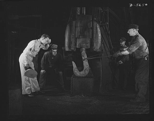 A poster comes to life. In a small blacksmith and maintenance shop on the mill grounds, Woolslayer and Sergeant Vineyard watch men at work on a drop hammer shaping a red-hot crane hook. Allegheny-Steel, Pittsburgh, Pennsylvania
