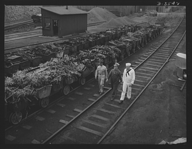 A poster comes to life. The men pass the scrap charge for a battery of open-hearth furnaces, piles into small buckets which are emptied into the furnaces by an electrically operated shoveling mechanism. The line of buckets at the left shows what is happening to the auto hubs, axles, and drive shafts which a few months ago were strewn over the countryside in auto graveyards. The bucket-line at the right contains mill waste, which is carefully saved and reused
