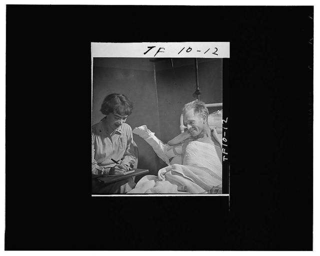 A Red Cross hospital recreation worker in an Army hospital in Great Britain, assisting a soldier whose right arm is in a cast , in writing to his relatives back home