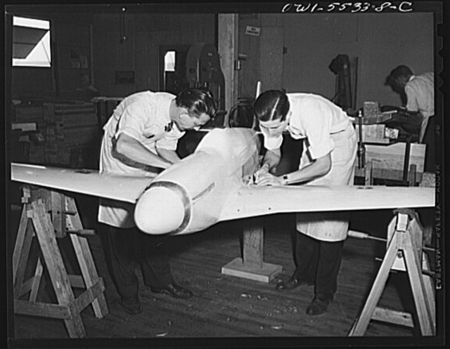 A scale wind tunnel model of North American Aviation's P-51 fighter is prepared by two model shop employees before another test is made to determine its flight characteristics. All measurements on these models are within two thousandths of an inch