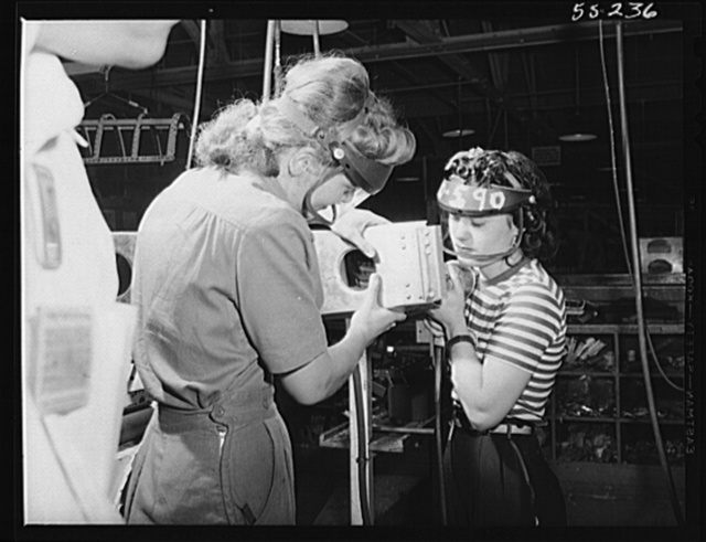 A section for the wing of a P-51 fighter is assembled by these two women employees at North American Aviation