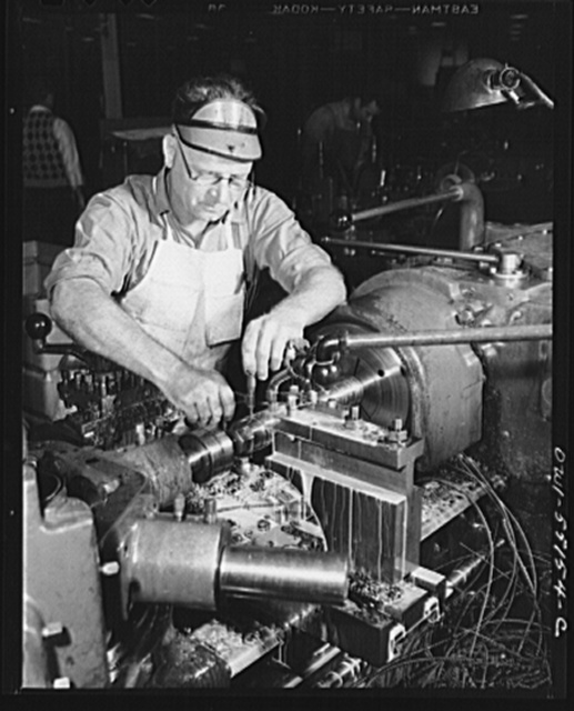 A skilled machinist on a turret lathe in North America's machine shop tests the accuracy of his work with a micrometer