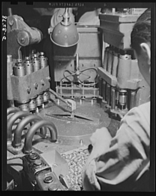 A special automatic machine in a converted cash register factory handles the operations of countercoring, disc inserting, crimping and unloading 20mm fuses. National Cash Register Company, Dayton, Ohio