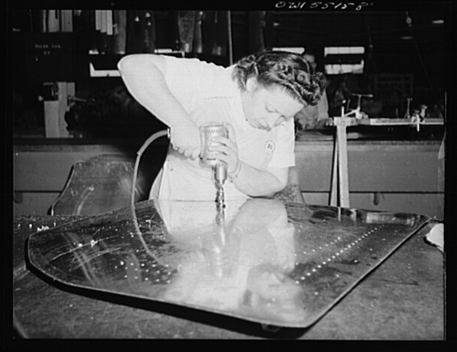 A woman employee in North American's sheet metal department counter-sinks holes prior to riveting
