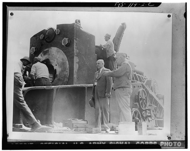 Aberdeen Proving Ground, Maryland. Major General Charles T. Harris, Jr., explaining the workings of the breech in a sixteen-inch gun to Congressman Andrew J. May, chairman of the House Military Affairs Committee. Mr. May saw the huge gun fired, then toured the proving ground, and examined mobile artillery, small arms, and other ordnance material
