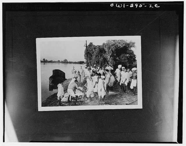 Agra (vicinity), India. American soldiers sightseeing near the Taj Mahal come upon a Hindu burial service and watch the remains being prepared for the funeral pyre. Standing in the background left to right are: Private First Class John C. Byrom, Jr. and Corporal Louis J. Ryba