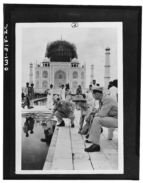 Agra (vicinity), India. Private First Class John C. Byrom, Jr., of Waco, Texas, trying to catch a goldfish in the marble-lined pool at the approach to the Taj Mahal. Observing are Corporal Anthony J. Scopelliti and Private First Class Ray Cherry