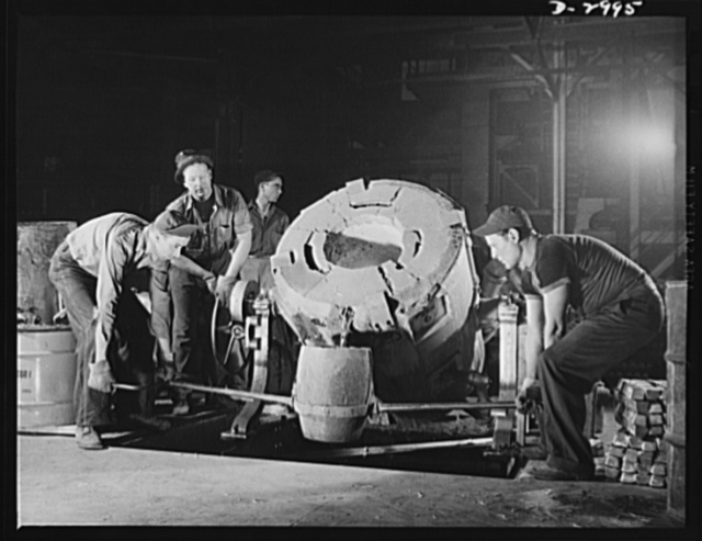 Aluminum casting. Sturdy workers in an aluminum plant pictured as they tap a 450-pound tilting-type crucible furnace to pour the molten into smaller gats from which further pourings are made. The finished product will be sent to a converted automobile factory or to an Eastern manufacturer of bomb sights. Specific destination for the aluminum parts is secret. Aluminum Industries Inc., Cincinnati, Ohio