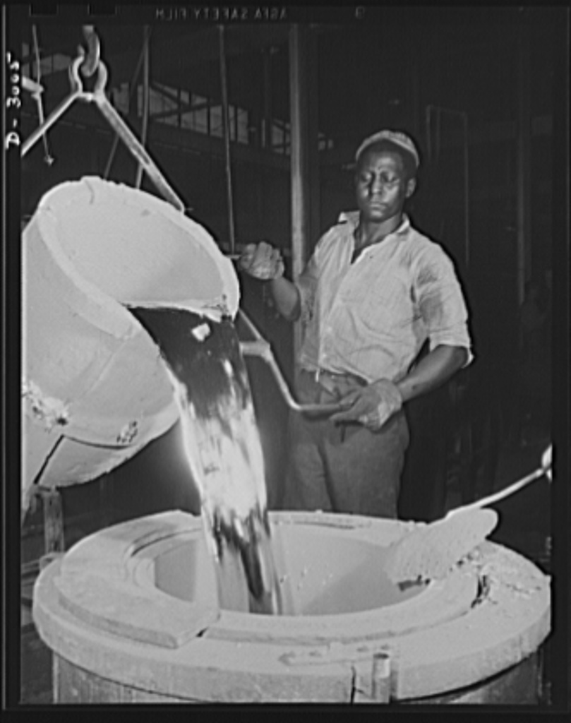 Aluminum casting. This bright white hot riser of aluminum is being poured from a 300-pound pot to a 300-pound holding pot. Molders will dip this holding pot to make castings. Aluminum Industries Inc., Cincinnati, Ohio