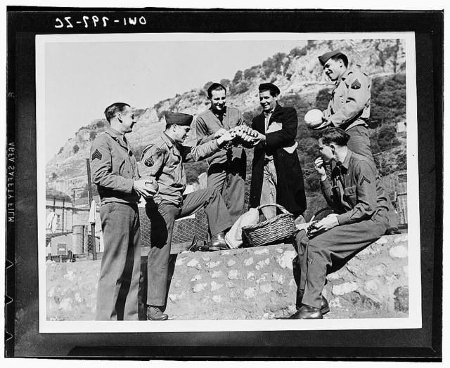American troops in North Africa sample the wares of a fruit vendor. Left to right: Sergeant Hardy Patillo of Austin, Texas; Captain Louis Dubcak of Lexington, Texas; Sergeant Adan Garza of Laredo, Texas; and Private First Class Herbert Lipsey of Dade City, Florida