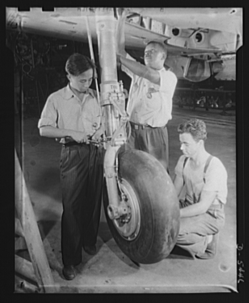 Americans all. At an Eastern aircraft factory, Philip Leung, Chinese; Marcell Webb, Negro; and an unidentified white worker adjust the retractable landing gear of a pursuit plane on the final assembly line. Republic Aircraft Corporation