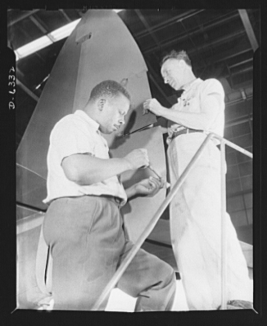 Americans all. In the armed forces and on the production line, Americans of every race and creed fight shoulder to shoulder to defeat the forces which threaten to destroy our liberties. Here Charles Geier (right) and Marcell Webb work on the rudder of a P-47 pursuit ship in an Eastern aircraft factory. Republic Aircraft Corporation