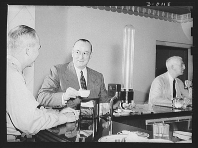 America's production chief. Donald Nelson, America's production chief, streamlines his personal life just as he streamlines the war effort on the home front. Before buckling down to his huge daily task as chairman of the War Production Board (WPB), Mr. Nelson snatches a 7:30 breakfast in the coffee shop of his hotel where he occupies a simple three-room apartment