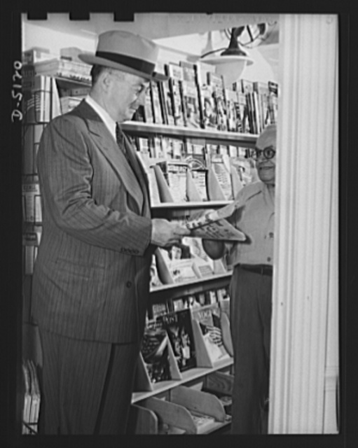 America's production chief. Keeping tabs on the fighting fronts is an important part of Donald Nelson's job as War Production Board (WPB) chairman. He selects a morning paper to read in his car before departing for his office. Later in the day, he will go through the file of metropolitan papers in his office