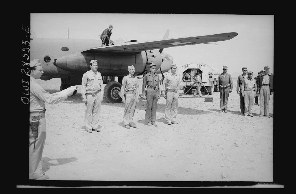 An Allied airbase somewhere in Nothern Africa. Four American airmen of the Bombardment Group, United States Army, Ninth Air Force, take just enough time out to receive their citations while their bonber is being refueled. They are shown as they lined up beside their B-24 just before General Auby C. Strickland made the awards. Left to right: Lieutenant Lorey H. Woods, pilot, 1381 Worton Boulevard, Cleveland, Ohio; Staff Sergeant Steve E. Rambert, twenty-one, gunner, 2321 North Parkade, Chicago Illinois; Technical Sergeant Wallace Armstrong, nineteen, Pittsburgh, Pennsylvania, 3515 Simon Avenue; Lieutenant Albert P. Miska, navigator bombardier, twenty-five, 449 Compton Avenue, Perth Amboy, New Jersey
