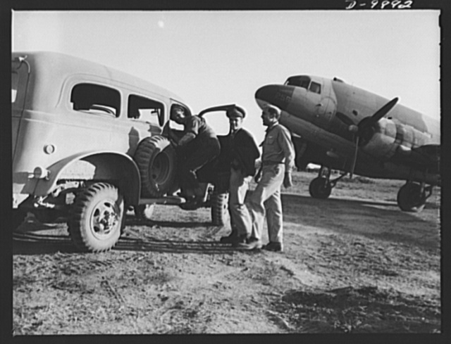 """An American flying squadron in India. Back from a flight from China, Lieutenant Ronald J. Fruda, West Palm Beach, Florida; Lieutenant Laurence D. Putnam, Portland, Oregon and radio operator Fishbaugh step into an army truck at the field to go to """"Happy Tavern,"""" the home where the twenty-two flyers are stationed"""