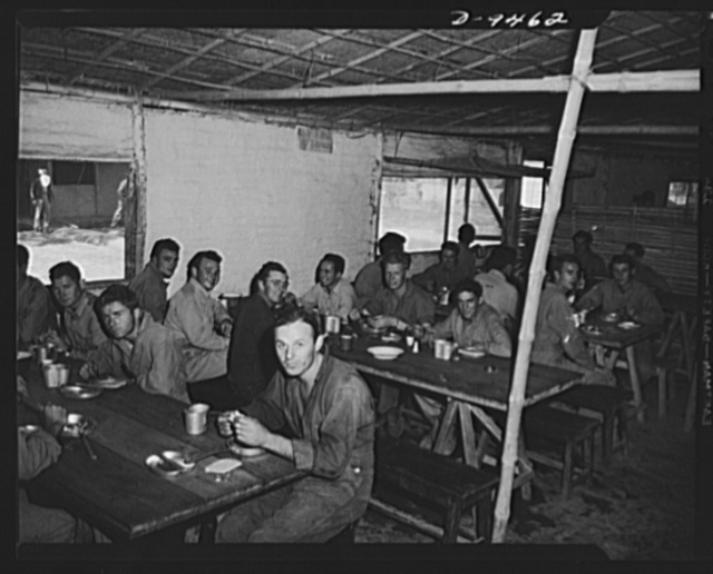 An American flying squadron in India. Chow time. While it's not the Astor it serves just as well for the food is good and second servings can be had. Most buildings in this camp were constructed by local labor but our boys have taken part in later construction, having learned many forms of handicraft from the natives themselves