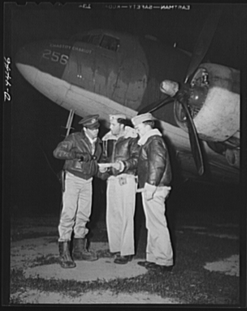 "An American flying squadron in India. Last minute instructions before ""Chastity Chariot"" takes to the air. Shown, left to right are: Lieutenant Jack O. McReynolds of Dallas, Texas, Lieutenant Richard J. Taylor of Redlands, California and Lieutenant H.W. Gessner of Eau Claire, Wisconsin. Today it was ""Mac's"" turn to ""take her off"" with Gessner as co-pilot"