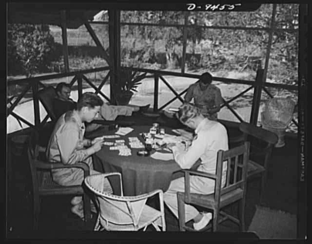 An American flying squadron in India. Leisure hours. Some play solitaire, some write and some read. Seated in front are, left to right: Lieutenant J.C. Crossett of Springdale, Washington, recently decorated by the Chinese government for dropping rice; and Captain John T. Johansson of San Jose, California. In background are, left to right: Lieutenant H.W. Gessner of Eau Claire, Wisconsin and Lieutenant Marion J. Rich of Trenton, New Jersey