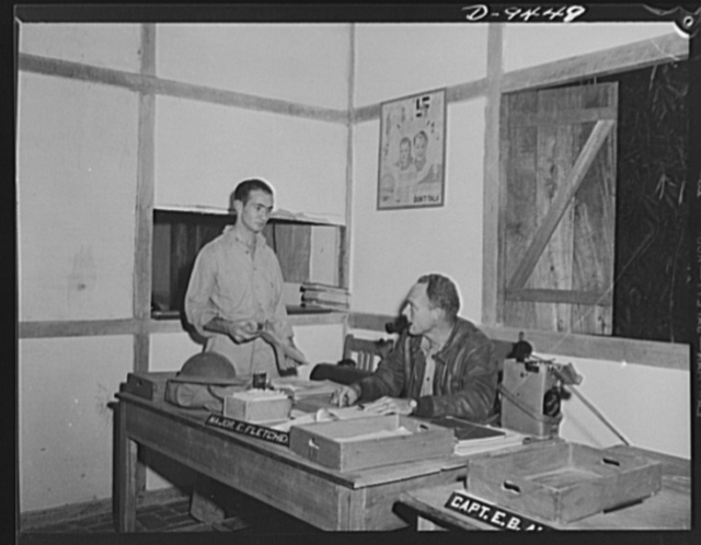 """An American flying squadron in India. Major E. Fletcher and orderly. Major Fletcher, """"Skipper"""" of the outfit, at his desk in the """"operation shack."""" He is from Kansas City, Missouri and has been in India for nearly a year"""
