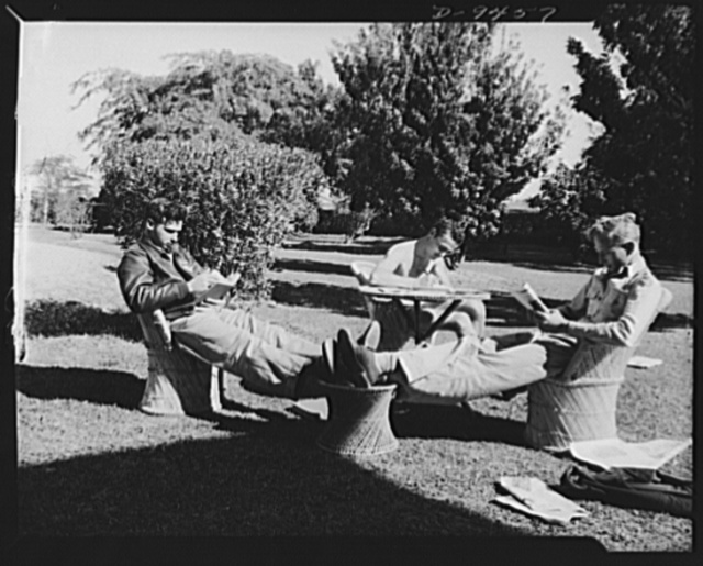 An American flying squadron in India. Taking it easy. Sitting on the lawn in rope chairs made by Indian natives, writing or reading becomes a pleasure. Shown, left to right are: Lieutenant Marvin Siegel of Chicago, Illinois; Lieutenant L.D. Putnam of Portland, Oregon and Captain J.T. Johansson of San Jose, California