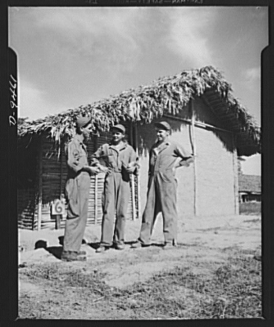 "An American flying squadron in India. ""What's cooking?"" asks Technical Sergeant J. Young of Pennsylvania, standing in front of thatch-roofed barracks No. 6, talking to Private F.S. Sirocks also from Pennsylvania and Corporal J.J. Conroy of Illinois, just before chow time"