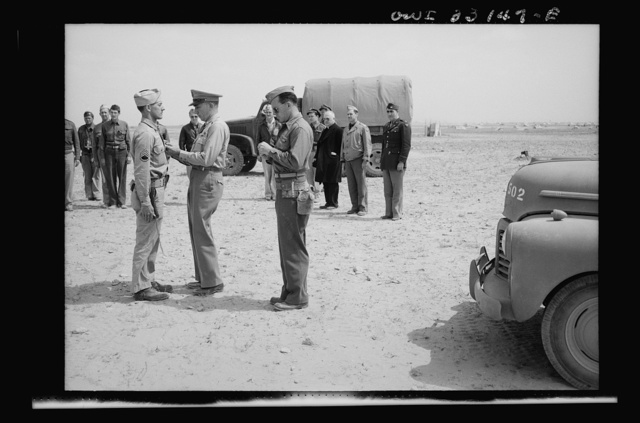 An American sergeant receiving a decoration during the North African campaign. Archbishop Spellman of New York is watching the ceremony