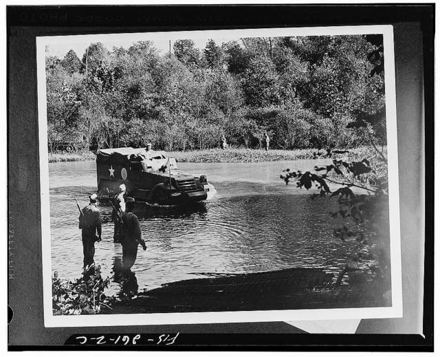 An armored half-track vehicle belonging to a medical unit fording the river during the Second Army's middle Tennessee maneuvers