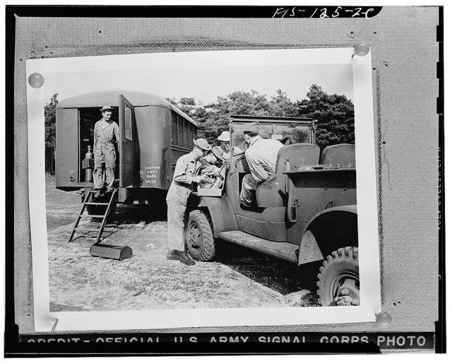 """An army truck being repaired at a mobile unit in England. Note the caution sign on this American vehicle from a """"keep to the right"""" country, now in a """"keep to the left"""" one"""