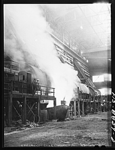 Anaconda smelter, Montana. Anaconda Copper Mining Company. Battery of converters; in near converter, copper is being poured into ladle. In the converter, impurities in the copper are removed by oxidation with air and the final product approximates 99.3% pure copper