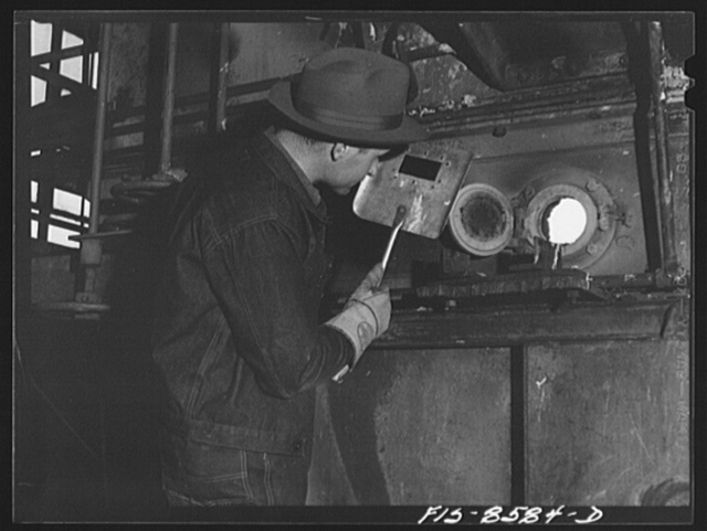 Anaconda smelter, Montana. Anaconda Copper Mining Company. Experienced workman watches the color of roasting manganese ore through oven door