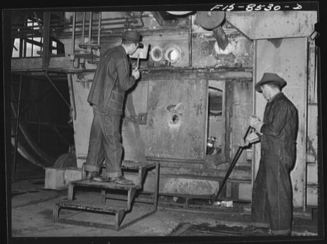 Anaconda smelter, Montana. Anaconda Copper Mining Company. Workman inspecting the roasting process of manganese ore, which is a carbonate of manganese called pink rhodochrosite