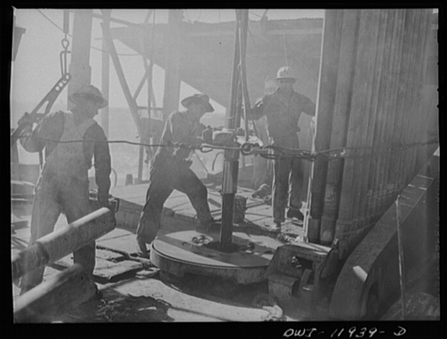 Andrews County, Texas. Unscrewing a piece of drill pipe by means of a rotary table. The pipe is being pulled out of the well to change the bit