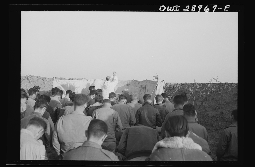 "Archbishop Francis J. Spellman of New York, on his recent tour of North African battlefronts, said mass for the men at the Fifty-seventh Fighter Group of the United States Army Ninth Air Force. This Air Force group is located ""somewhere in Tunisia"" and they are the boys who scored the biggest victory in the history of aviation, knocking almost 100 Axis transports and fighters out of the skies on one engagement. The archbishop held mass in a plane revetment at the Fifty-Seventh fighter base. The altar was set up and mass held on the spot. He said mass whenever and wherever there were boys who were interested in hearing one. Attendants at the mass were Major C.H. Logue, Catholic priest from Cleveland, Ohio, and Capptain J.E. McCarrity, Paulist priest from New York City and Air Force chaplain. They are seen in some of the pictures"