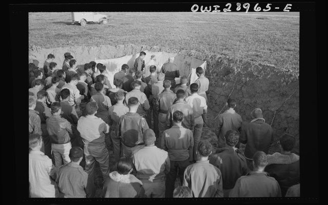 """Archbishop Francis J. Spellman of New York, on his recent tour of North African battlefronts, said mass for the men at the Fifty-seventh Fighter Group of the United States Army Ninth Air Force. This Air Force group is located """"somewhere in Tunisia"""" and they are the boys who scored the biggest victory in the history of aviation, knocking almost 100 Axis transports and fighters out of the skies on one engagement. The archbishop held mass in a plane revetment at the Fifty-Seventh fighter base. The altar was set up and mass held on the spot. He said mass whenever and wherever there were boys who were interested in hearing one. Attendants at the mass were Major C.H. Logue, Catholic priest from Cleveland, Ohio, and Capptain J.E. McCarrity, Paulist priest from New York City and Air Force chaplain. They are seen in some of the pictures"""