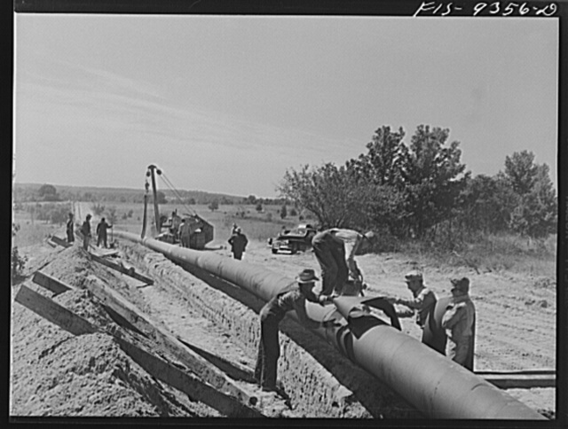 Arkansas-Texas state line to Gurdon, Arkansas. War emergency pipeline from Longview, Texas to Norris City, Illinois. Placing additional felt around piece of pipe which was found defectively wrapped by inspector