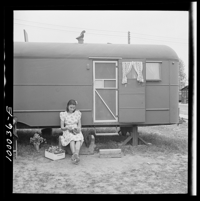 Arlington, Virginia. FSA (Farm Security Administration) trailer camp project for Negroes. Girl occupant preparing vegetables outside of a single type trailer