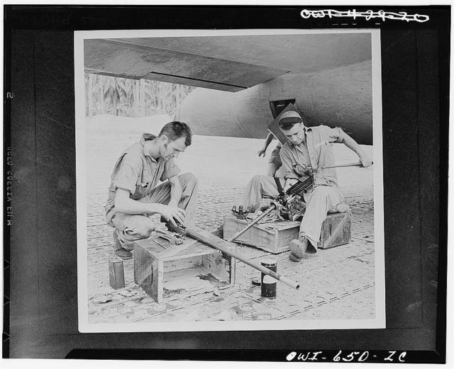 Back from a bombing attack on the Japs, these Flying Fortress gunners carefully clean their .50 caliber machine guns at a U.S. Army Air Force airbase in the New Hebrides. Left to right: Sergeant Edward T. Spetch of Seymour, Connecticut, and Sergeant Vernon Nelson of Fergus Falls, Minnesota