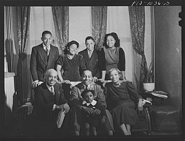 Baltimore, Maryland. Sargeant Franklin Williams, home on leave from Army duty, posing for family portrait with his mother and father beside him and his nephew on his lap
