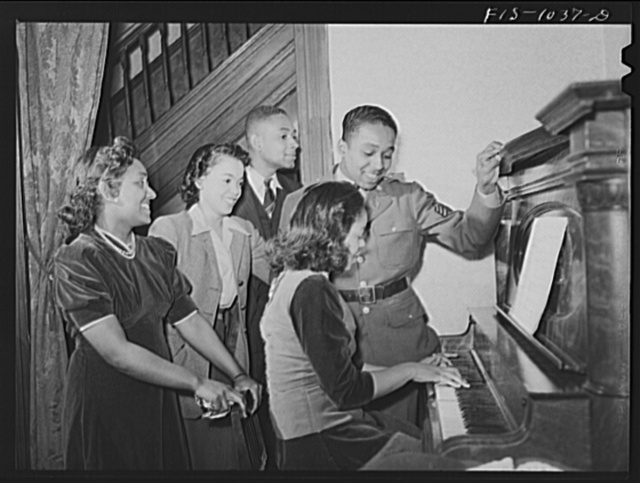 Baltimore, Maryland. Sargeant Franklin Williams, home on leave from Army duty, singing with his sister Sarah, his brother Thomas and his best girl Ellen Hardin while his sister Annetta plays the piano