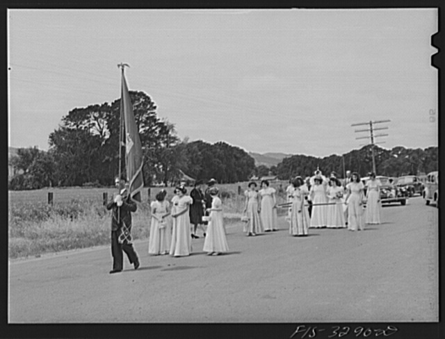 Banner of the I.D.E.S.I. society goes before the Queen in the parade of the Holy Ghost Festival of the Portuguese-Americans at Novato, California