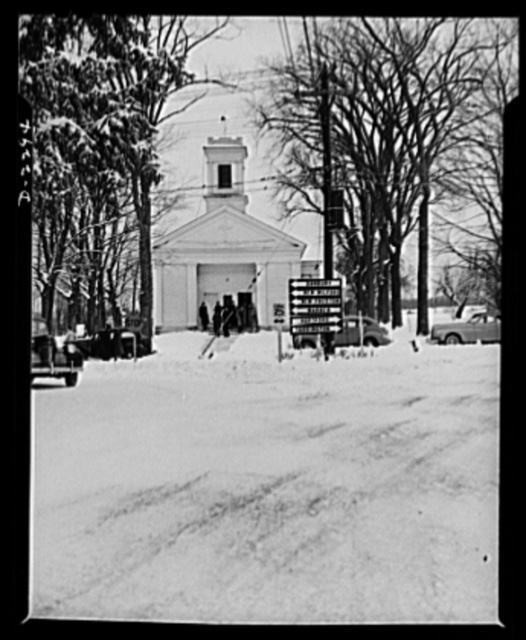 Bantam, Connecticut. 1942's first snow storm cut down attendance at the Episcopal Church, but even in good weather Bantam is not a community of churchgoers. Young Rev. H. Waldo Manly, who came to Bantam a few years ago from Washington, D.C., is president of the newly formed Bantam Lions Club. He says Bantamites live normal lives and are good neighbors. Arrest for anything other than traffic violations are practically unknown there. The tall man on the walk in front of the church is Spike Beves, a Warren McArthur sheet metal worker, who sings in the church choir. Spike, who now lives in Bantam with his wife and son, was formerly an insurance investigator in Brooklyn, New York