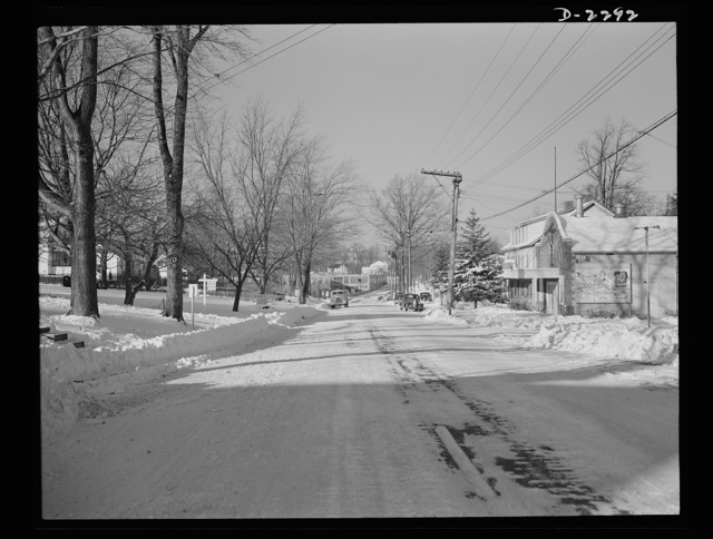 Bantam, Connecticut. Bantam Lane, looking toward the Warren McArthur plant and the center of town. To the left, now shown, are the new defense housing development and the Dante Electric Shop. In the right foreground is the Bantam theater. Blocked by the house next to the theater is the grocery store of Albert H. Bachman, who came to Bantam two years ago from Torrington; back of this one the tavern of Jack Fabri, and the Washington Supply Company, which deals mainly in feed, grain and coal